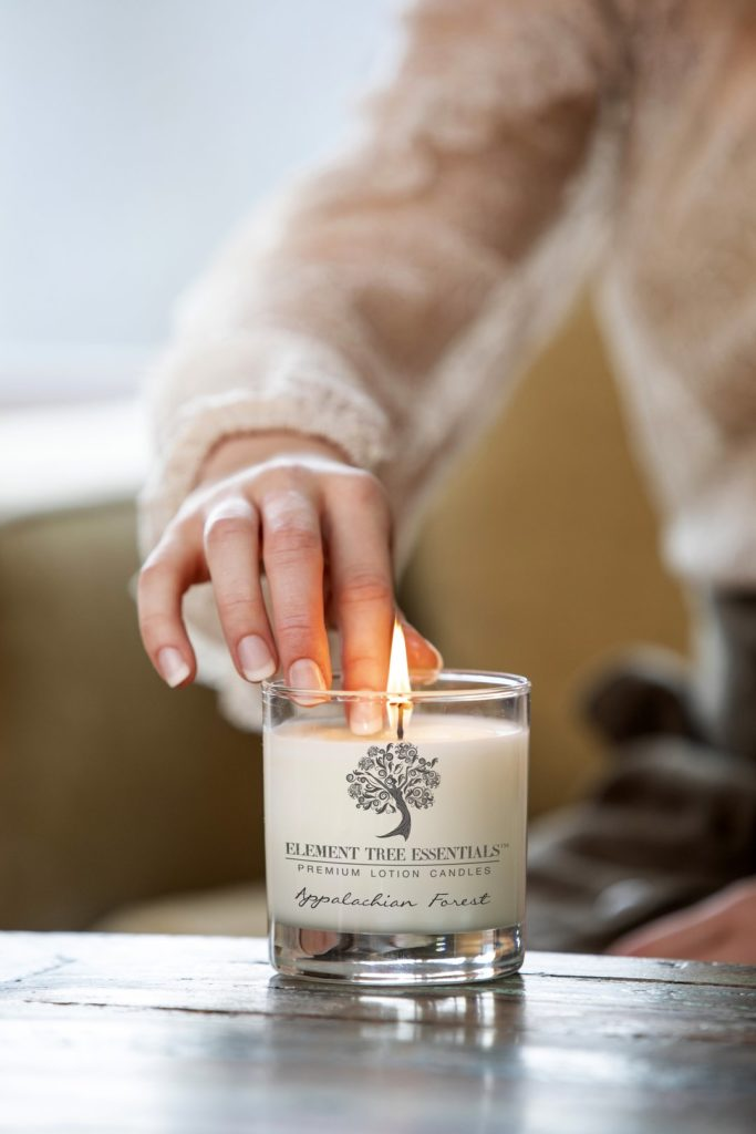 Photo of a hand touching the wax of a lit lotion candle from Element Tree Essentials.