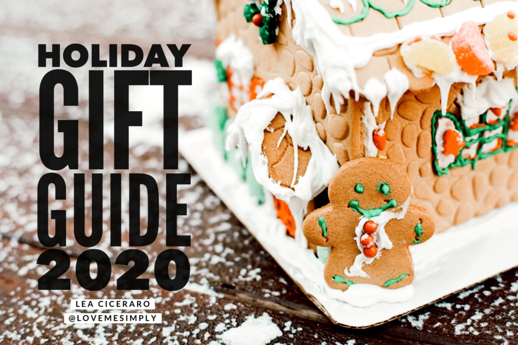 Gingerbread house in the snow with the words Holiday Gift Guide 2020 written on the left side. Title image for this blog post.