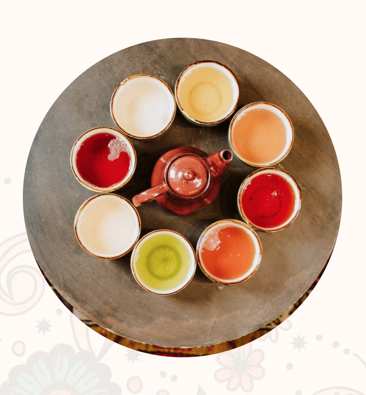 Top down photo of 8 tea cups with various colors of tea arranged in a circle around a red tea pot on a wooden table.