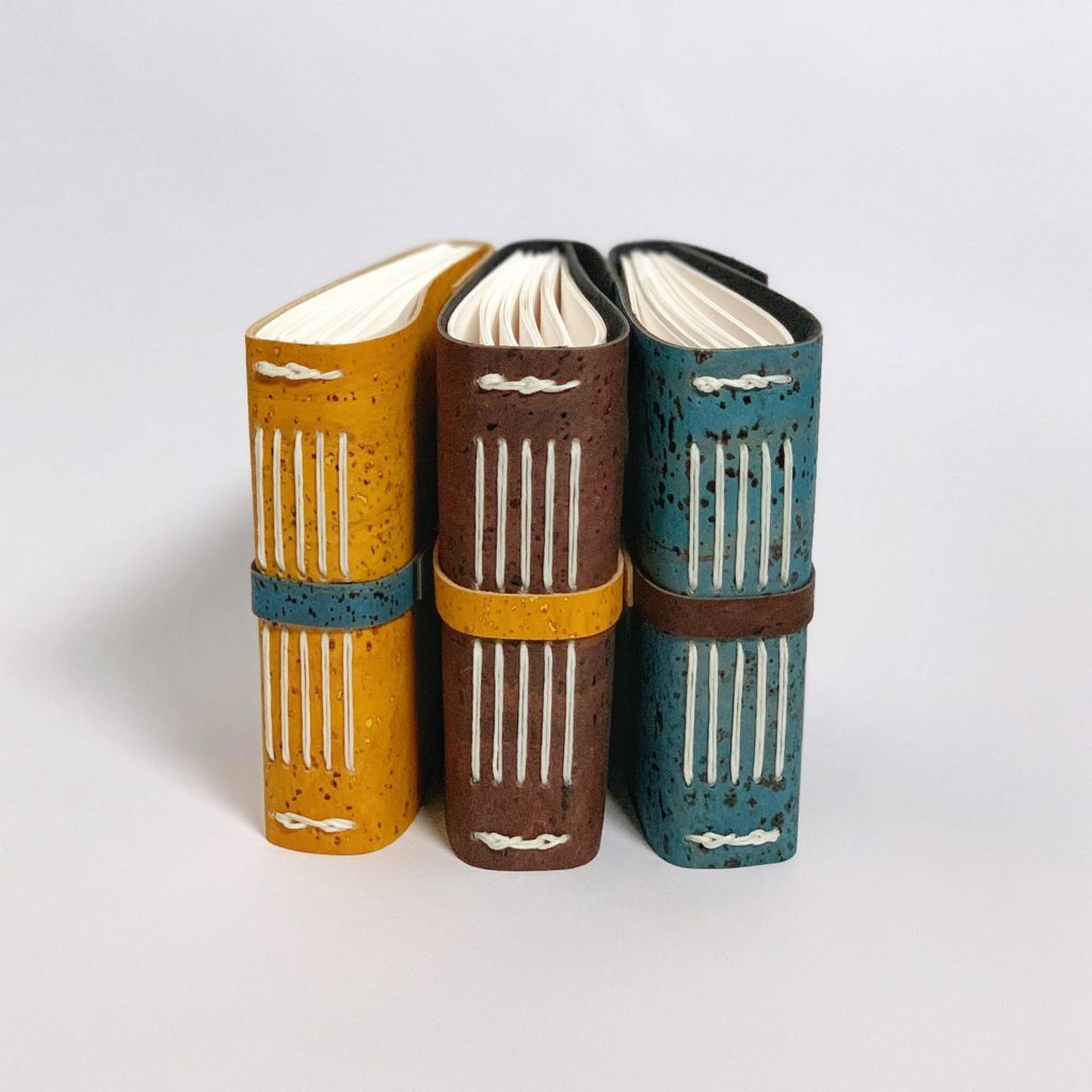 Photo of three handmade cork covered blank journals, in yellow, brown, and blue.