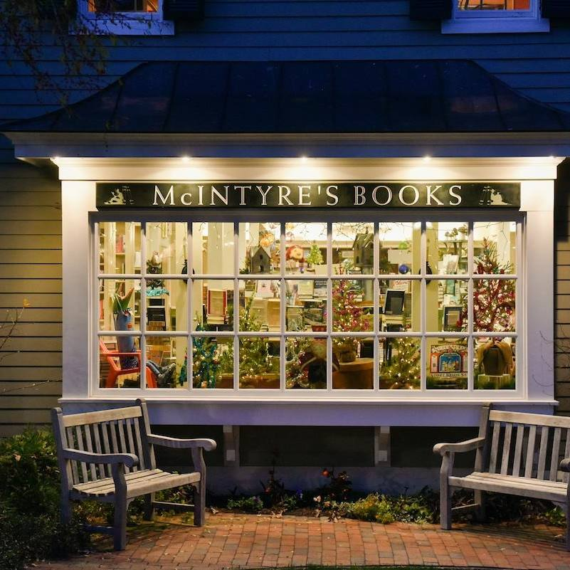 A photo of the front of McIntyre's Books in Pittsboro North Carolina in the evening and lit up looking through the shop window.