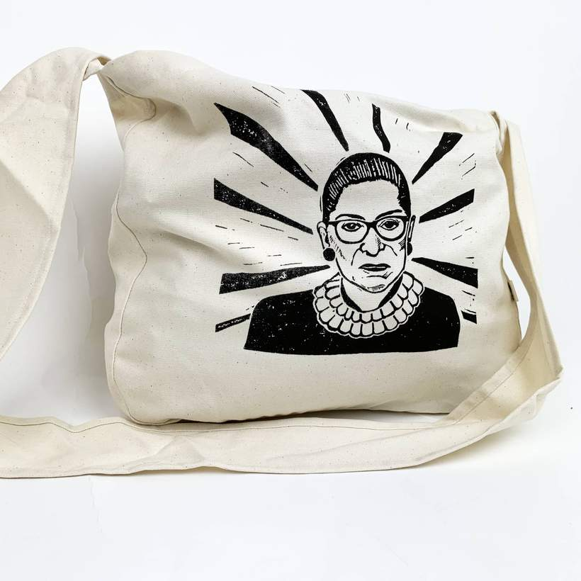 Photo of a canvas bag screen printed with a hand drawn image of Ruth Bader Ginsberg across the side.