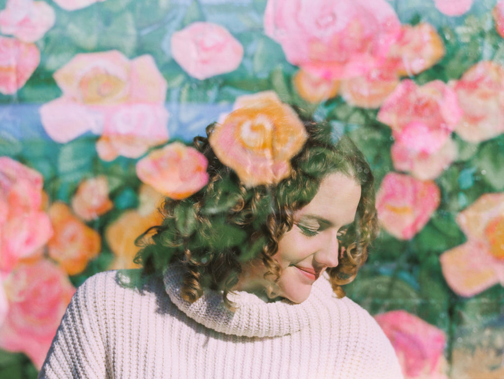 Photo of woman with curly hair in a white sweater against a wall of painted roses as a mural